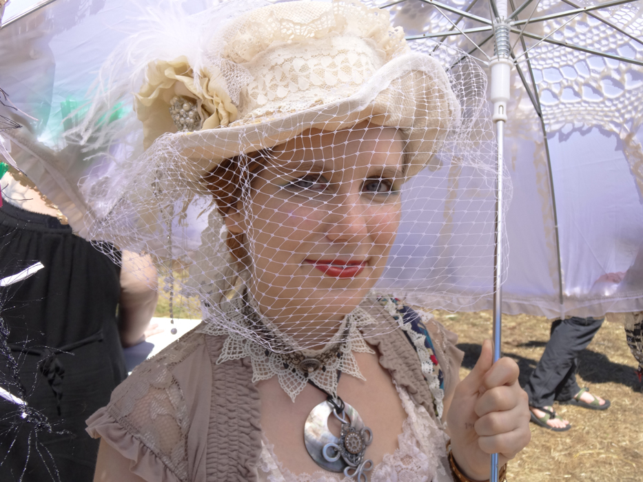 steampunk author photo with handcrafted top hat, parasol, necklace and lacy things.